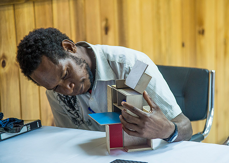 Mr Mevan Gera, Tainabuna Village School Board (Treasurer) inspects the 1:5 scale model of School-in-a-Box at a presentation held in Tufi, May 2015.   Photo © Zoe Reynolds