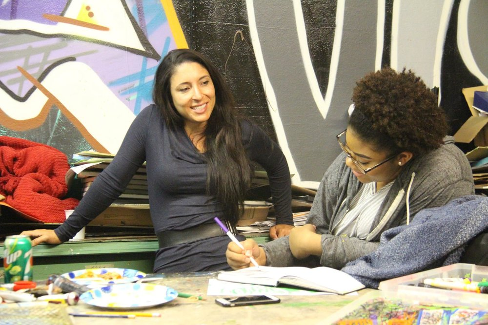 Tasha is pictured here working with a friend and mentee at Fabitat (A Space for Creativity).