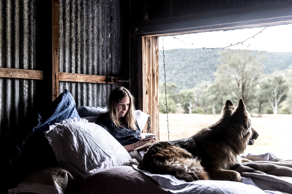 Lean and her dog Taj hanging out in a bed covered with In The Sac linens in the woolshed.
