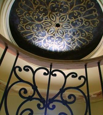 In this mid-production shot of a rotunda style foyer, you can see, we incorporated a ceiling pattern that reflected the ironwork on the stair rail spindles. The ceiling was finished in a chocolate Venetian Plaster and embossed with a metallic gold Venetian Plaster.
