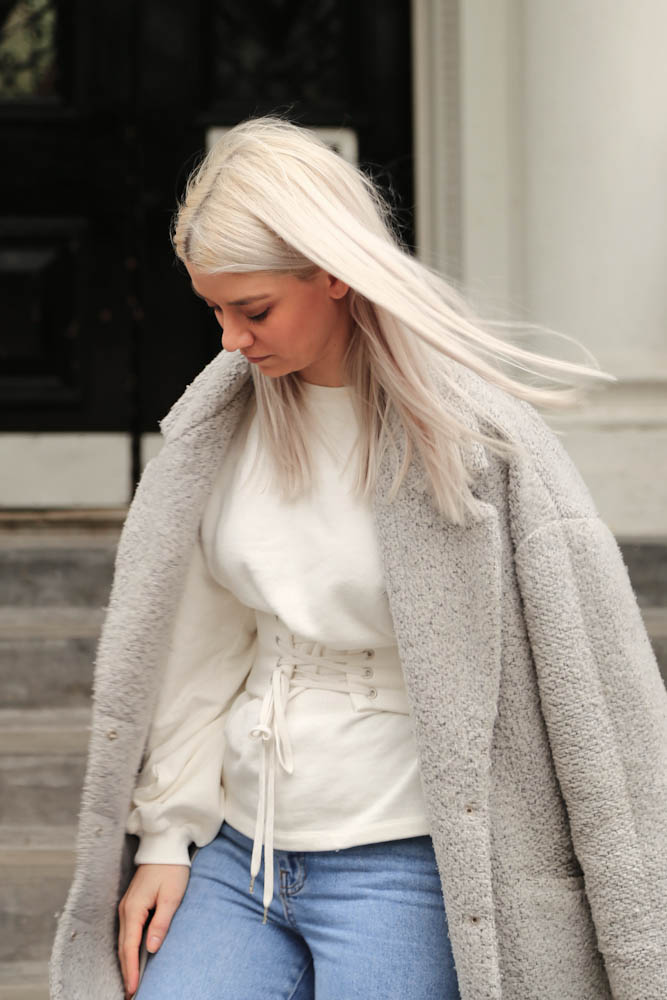 white blonde hair, cream sweatshirt, jeans, grey wool coat, northern magpie