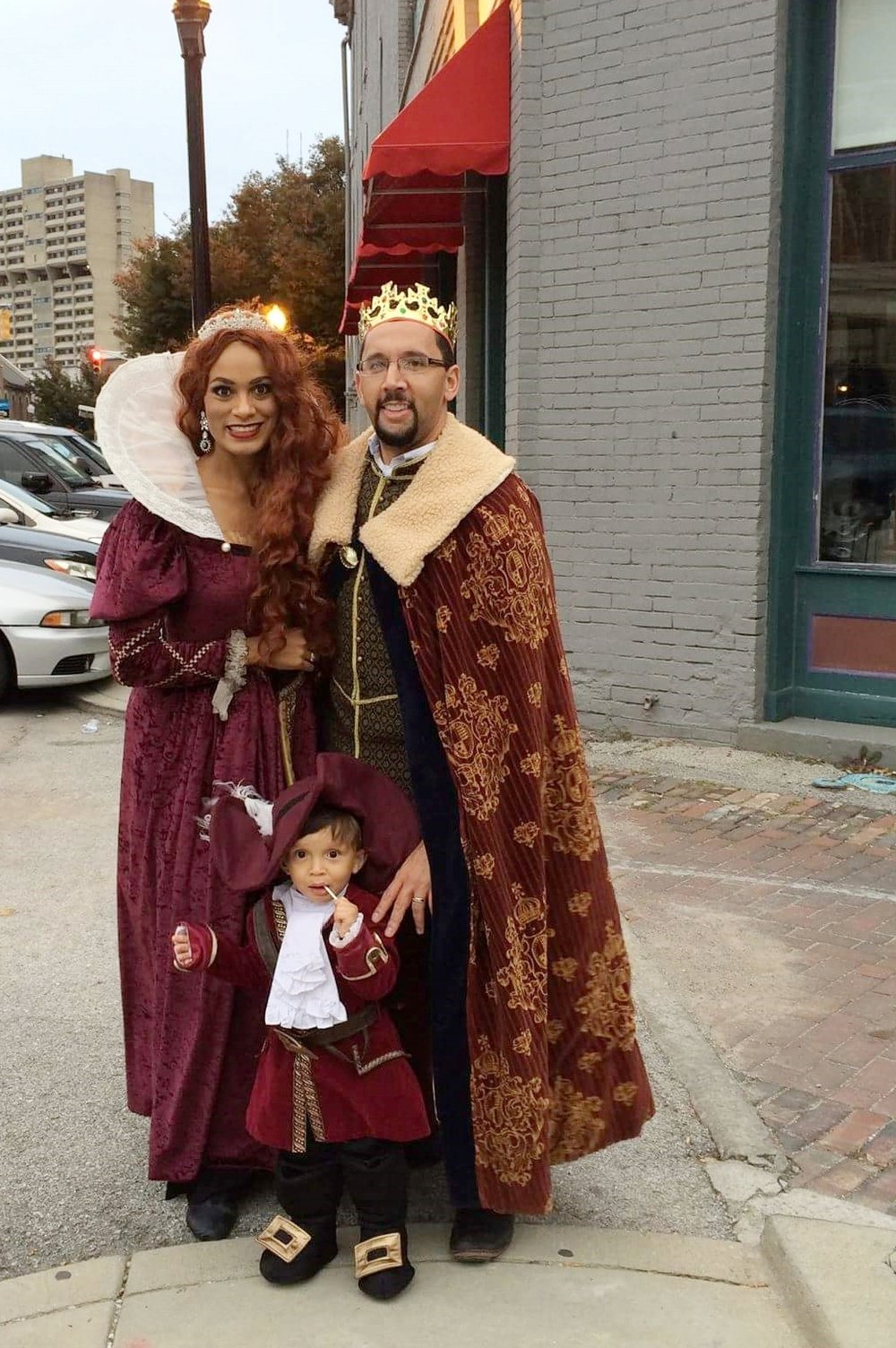 Amy, Kris and their toddler trick-or-treating on Mass Ave in 2016.