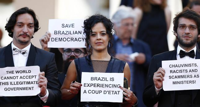 Brazilian actress Maeve Jinkings holds a sign reading 'Brazil is experiencing a coup d'etat' as she leaves after the screening of 'Aquarius' during the 69th annual Cannes Film Festival, in Cannes, France, 17 May 2016. Image credit: Daily Sabah.
