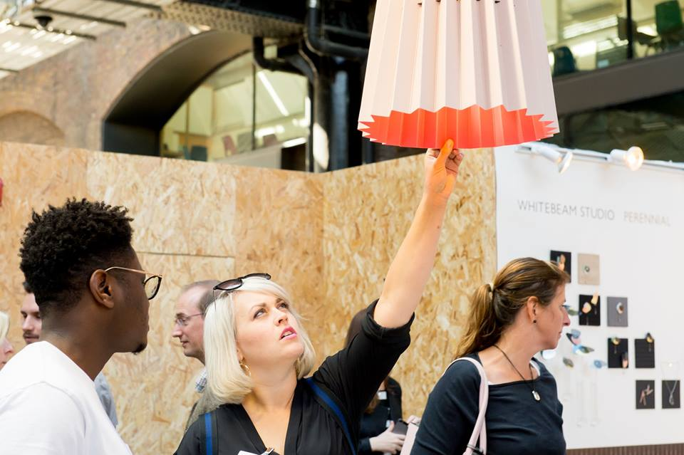 Customers admiring the Twin Tone Lampshade at the Little Greene stall. Photograph for Design Junction by  Ruth Ward .