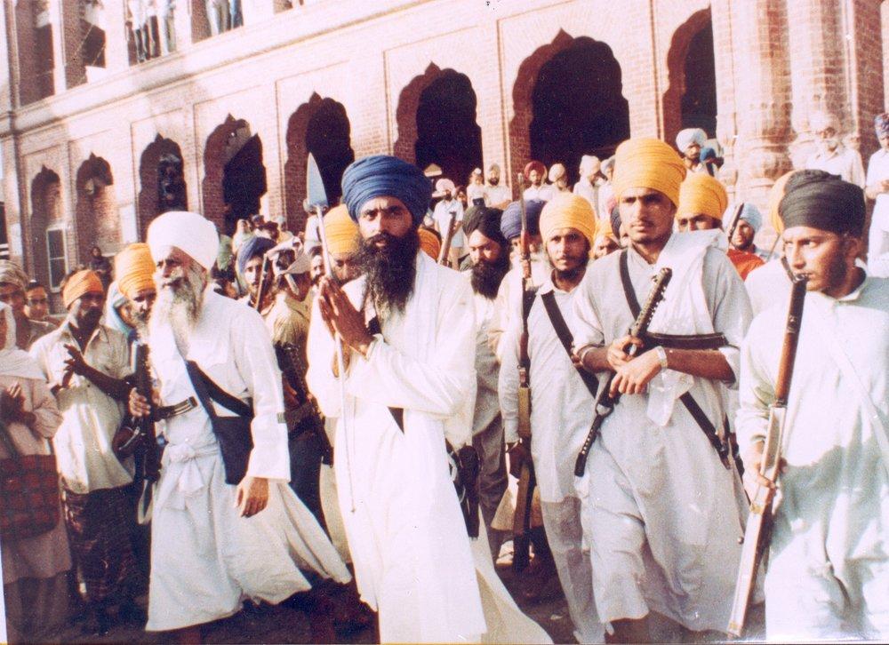 Shaheed Sant Jarnail Singh in Darbar Sahib surrounded by shastardhari Sikh naujavan.