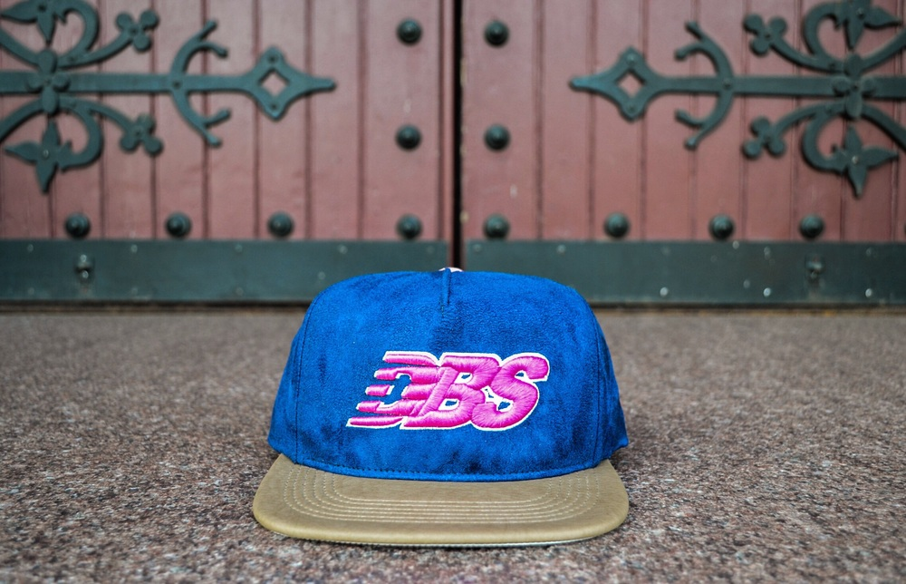"The newly released DBS ""Daytona"" Snapback used a New Balance inspired logo combined with inspiration from the popular Ronnie Fieg x New Balance 1600 ""Daytona"" sneaker."