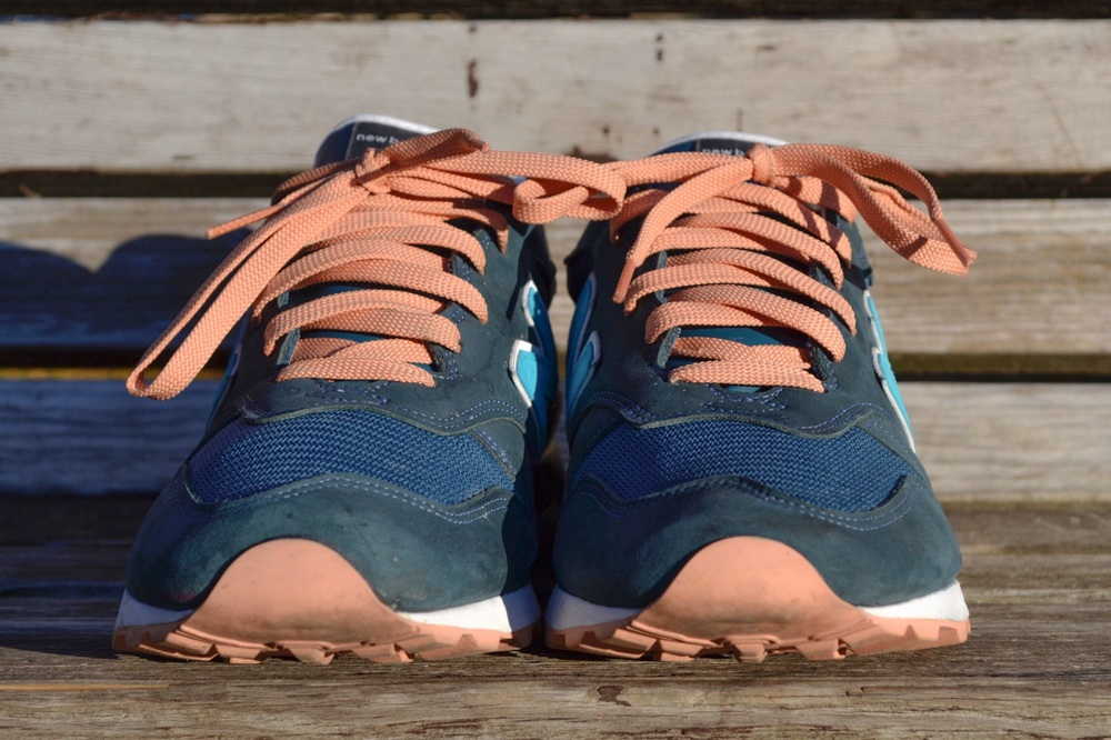 "Ronnie Fieg used a mixture of navy blue, grey and teal nubuck along with salmon accents to create the New Balance 1300 ""Salmon Sole""."