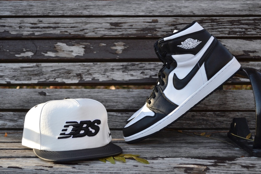 The Air Jordan 1 OG High Black/White with the matching White/Black Vinyl Runner Snapback.