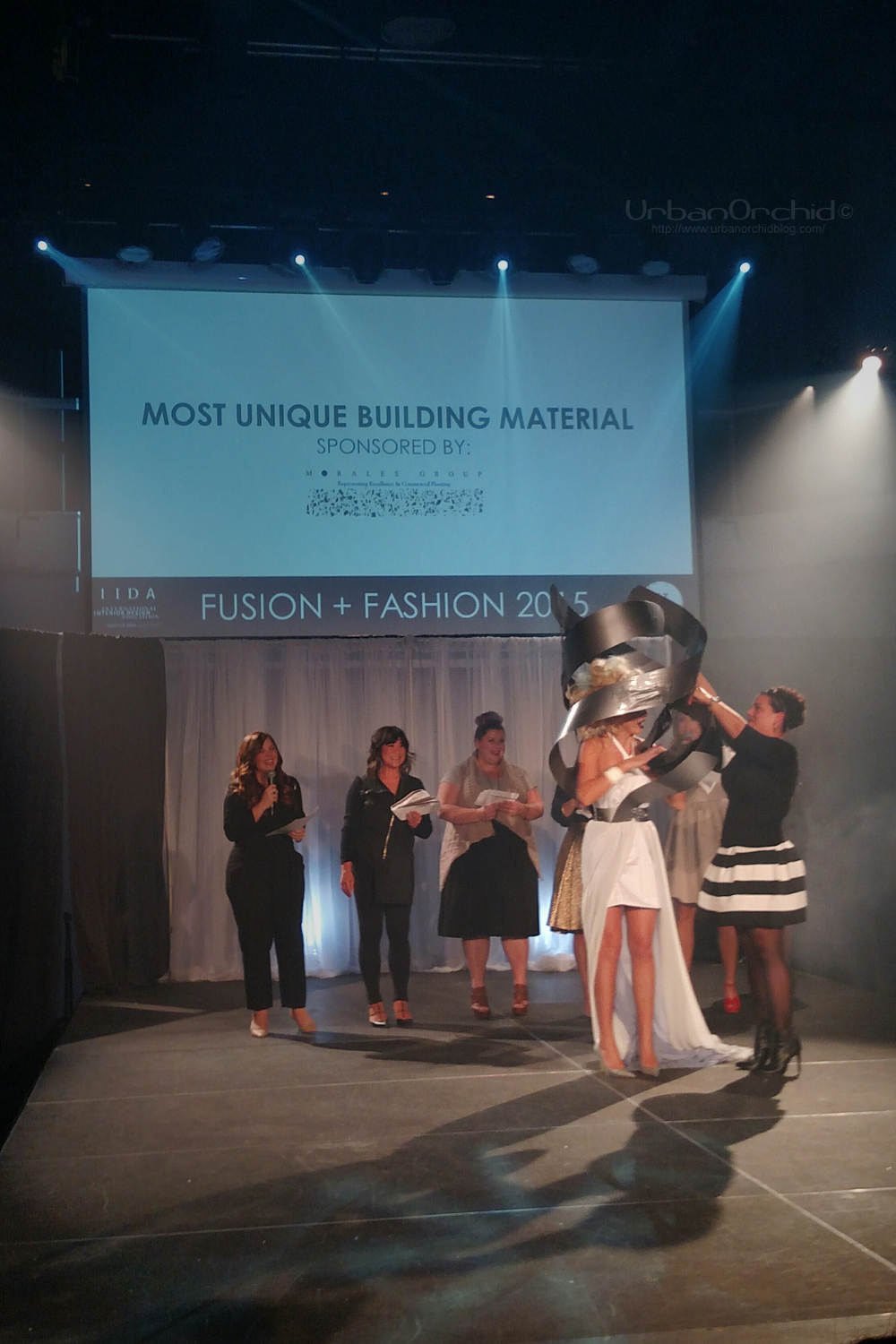 """Christine accepting the award sash for """"Most Unique Building Material""""."""