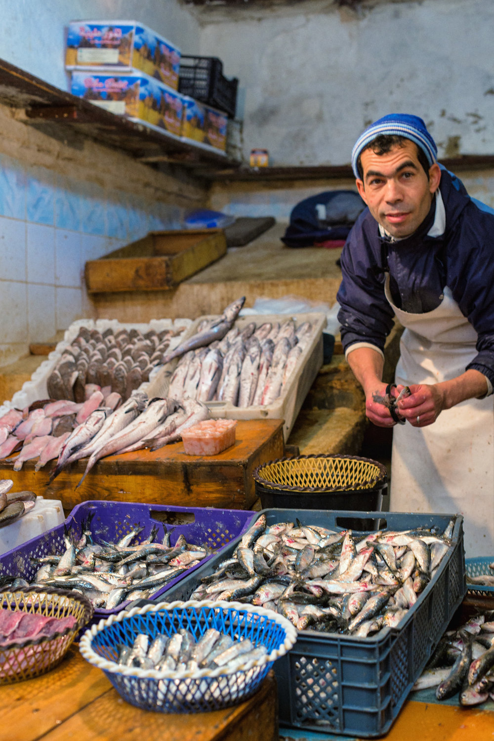A fisherman in the Fes souk looks up from cleaning the day's catch.