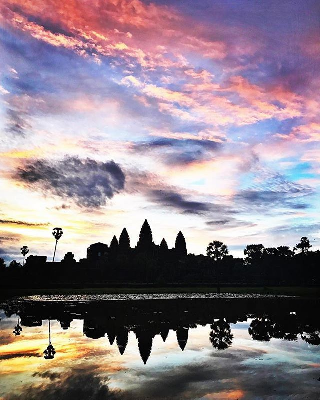 """Woke up this morning at 3:30am tempted to push snooze on my alarm and give up on the Angkor Wat sunrise. However, I embraced the power of opposite action by forcing myself out of bed and on a bumpy Tuk Tuk. Walking across the water and towards the temple, I witnessed this slap you in your face greeting from the sun. The only thing I remember is repeating, """"Angkor, WHAT?"""" And during those pauses, the World definitely spoke to me and said, """"Wake Up, you're alive."""" #SiemReap #Cambodia #remoteyear 