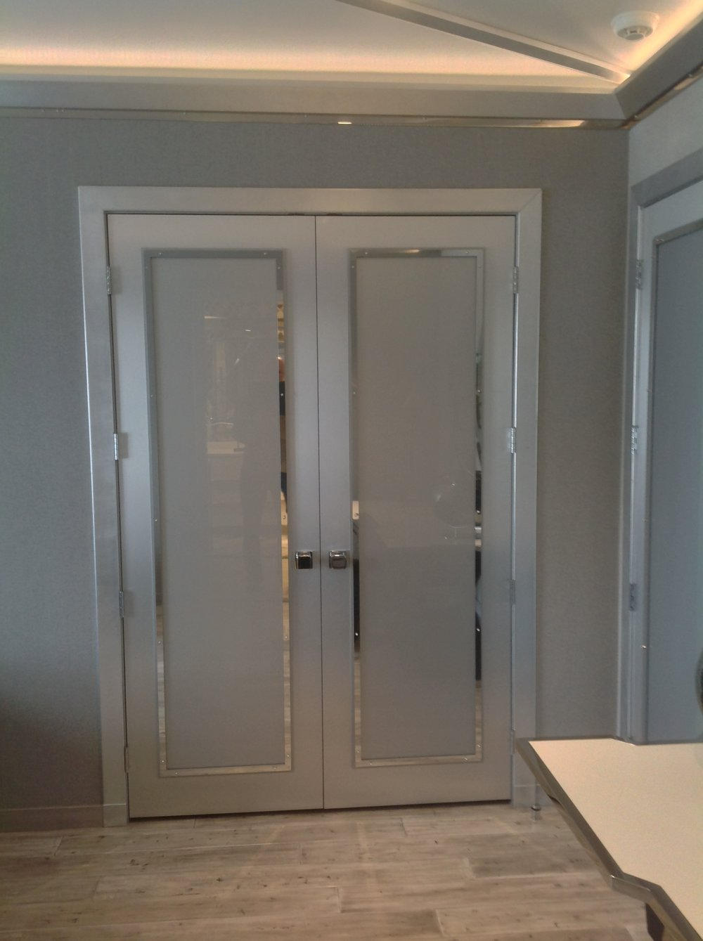 polished chrome and acrylic closet doors with silver leaf casings