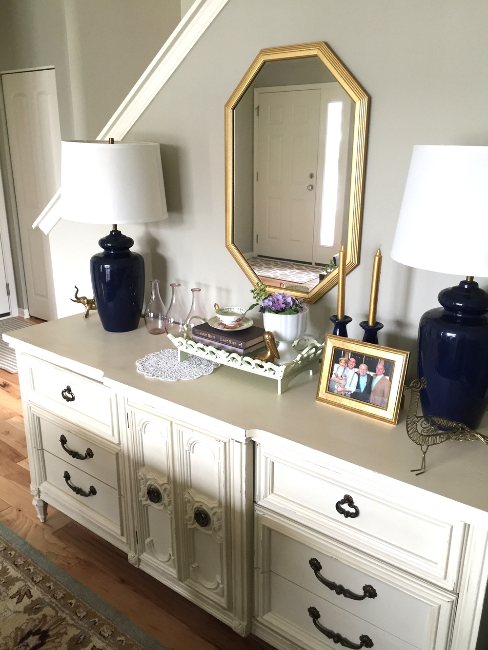 This is a more recent photo of the buffet. I picked up that mirror from a garage sale earlier this summer. The shape kind of mimics the shape of the chandelier in the room. I like to change up the styling with the seasons. [can you believe that everything you see in this photo was thrifted?]