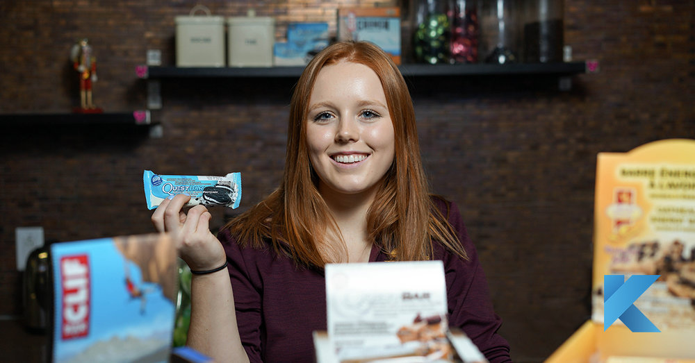 young woman holding protein bar snack at Beaconsfield