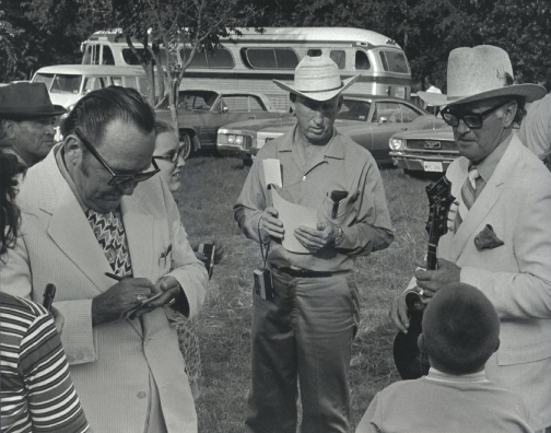 From the Archives:  Lester Flatt and Bill Monroe signing autographs in Garland, Texas 1971.  Photo by Ron Petronko.
