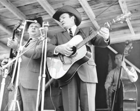 From the Archives:  Ralph and Carter Stanley (John Palmer on bass) at the Roanoke Blue Grass Festival in Fincastle, Virginia 1965.   Photo by Ron Petronko.