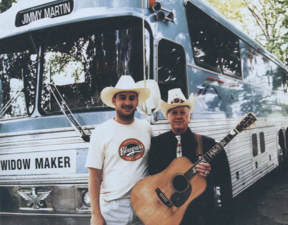 From the Archives:  Jimmy Martin and Road Manager Mark Goydos in front of the bus, Widow Maker,  Source unknown.