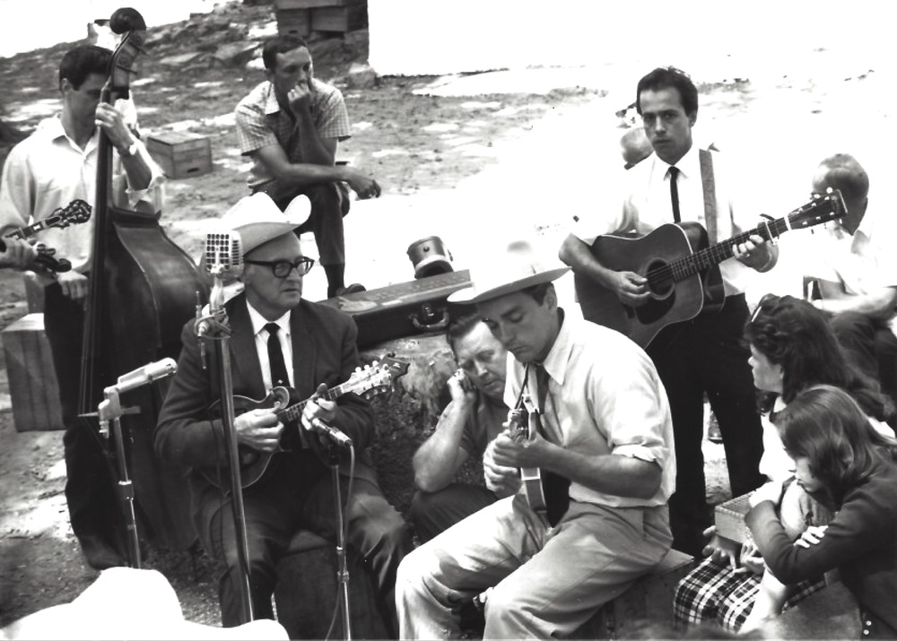 From the Archives:   Bill Monroe, teaching, James Monroe, Carlton Haney, Skip Gorman and Roland White at Berryville, Va. Photo donor unknown.