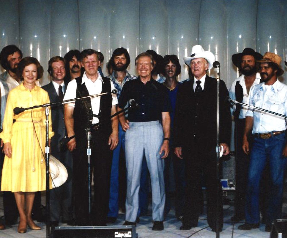 "From the Archives:  Bill Monroe on outside stage at night  standing with, first row from left to right, First Lady, Mrs Jimmy Carter, Doc Watson, President Jimmy Carter, Bill Monroe and unidentified man.  A group of unidentified people can be seen standing behind them.  The occasion was ""A Georgia Barbecue"" hosted by President and Mrs Jimmy Carter at the White House on 7 August, 1980.  Donated by the Jimmy Carter Presidential Library and Museum."