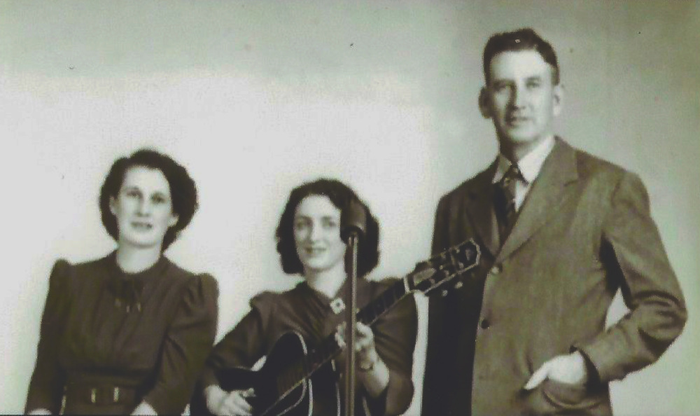 Sara and Maybelle Carter, at a microphone, Maybelle with guitar.  A.P. Carter standing to her left (right of the picture).  Donated by Jimmy Maynard.
