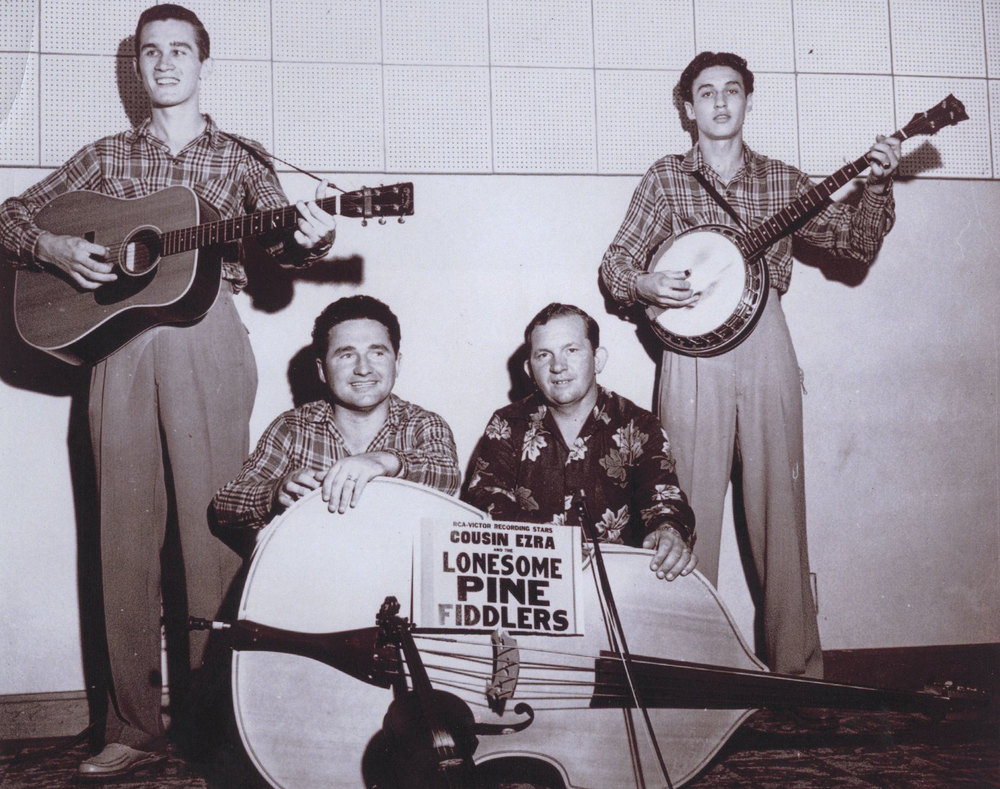 From the Archives:  Cousin Ezra and The Lonesome Pine Fiddlers showing Melvin Goins standing at left holding guitar, and Ray Goins standing at right with banjo.  Ray Cline and Ezra Cline are pictured kneeling in between the Goins brothers.  Taken at WLSI, Pikeville, Kentucky about 1956. Photo donated by Scotty Cline.