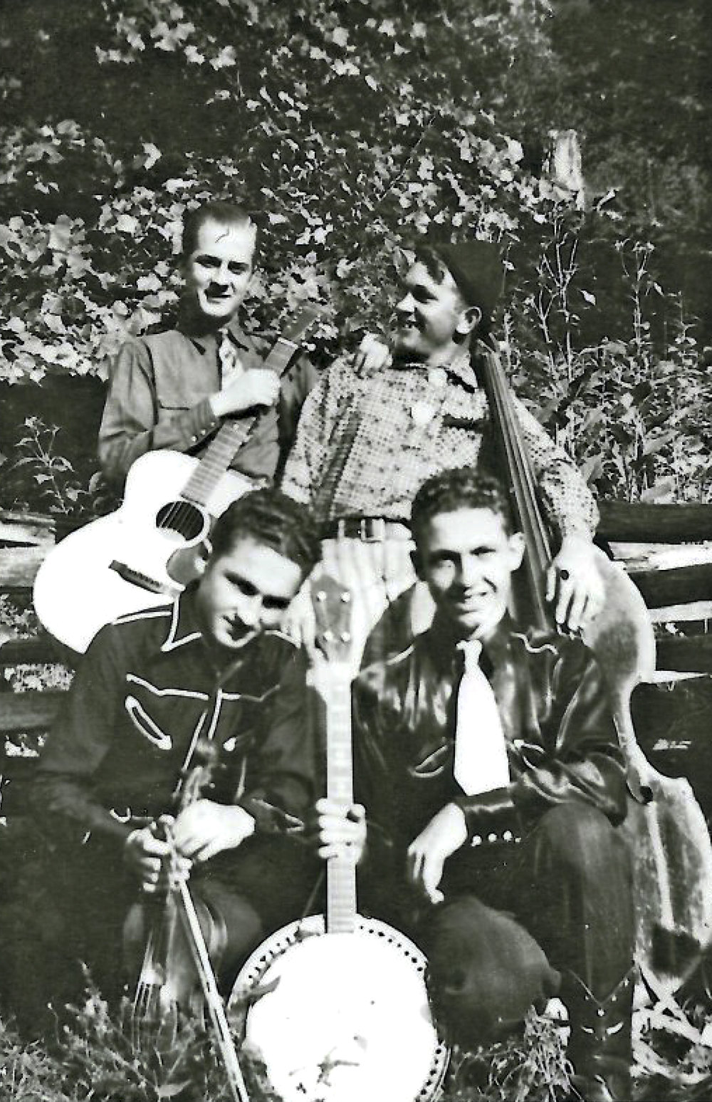 From the Archives:  Early incarnation of The Lonesome Pine Fiddlers taken at Gilbert  Creek, West Virginia in 1938.  Front, Ray and Ireland Cline (brothers); back, Zeke Stepp, Ezra Cline in comedy outfit.  Donated by Scotty Cline.