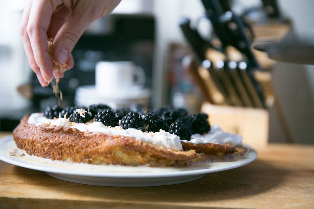 Sprinkling roasted coconut onto blackberry pie