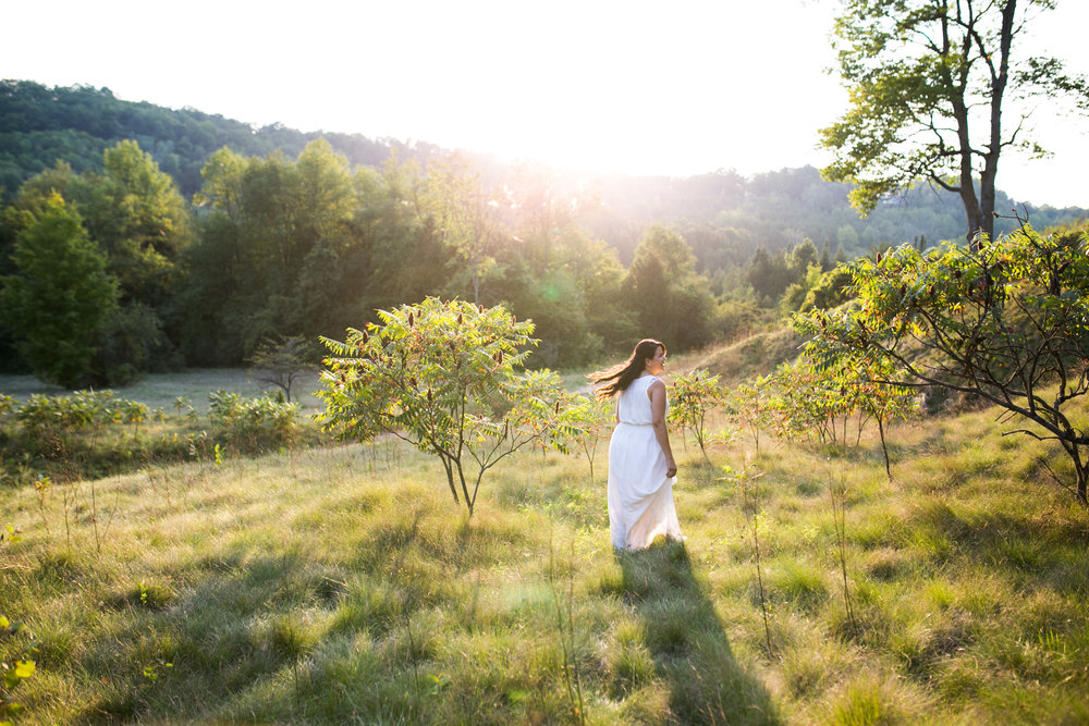Woman standing in field with flowy white dress