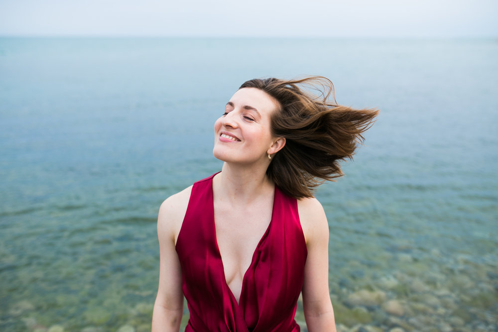 Woman by water with hair blowing in wind