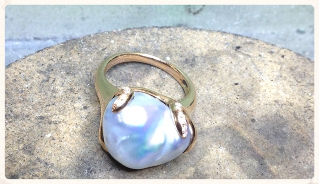Large blue-gray keshi pearl in swirled rose gold mounting accented with diamond melee.