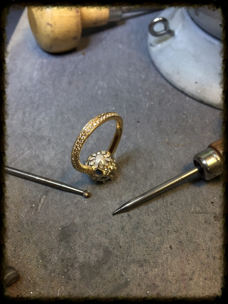 The ring with some tools of the trade, which include a ball bur for setting and a #0 beading tool.