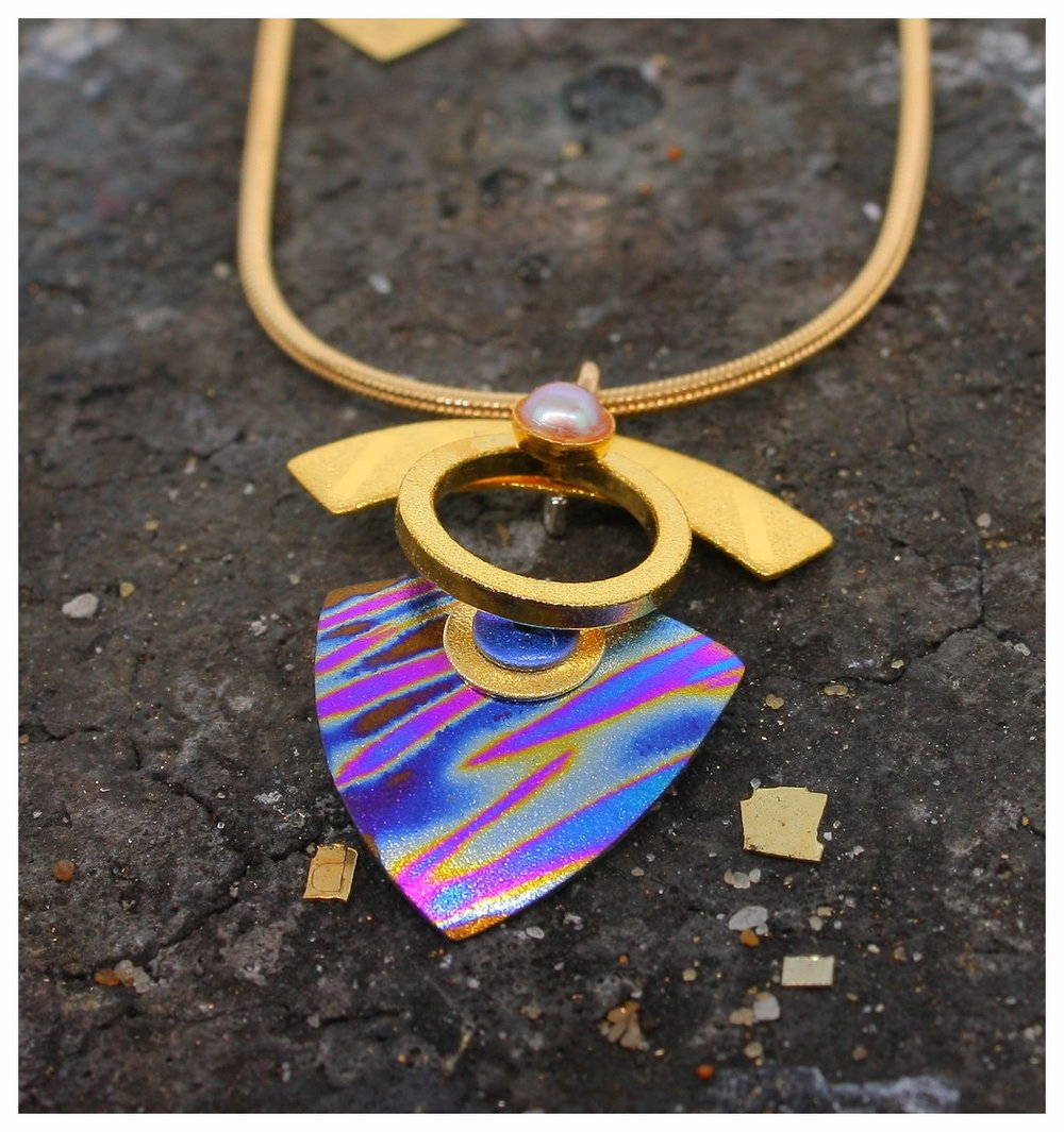 This niobium pendant is anodized to create a wave pattern in blues and fuchsia.