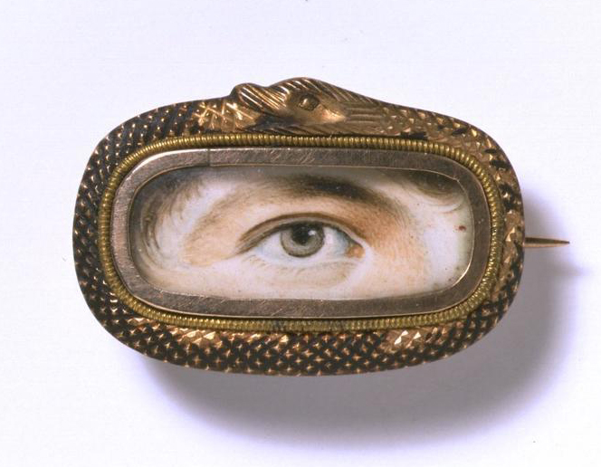 This eye miniature features a brownish-yellow iris, probably belonging to a man, surrounded by an oblong frame shaped as a snake swallowing its tail. From the Victoria & Albert Museum in London.