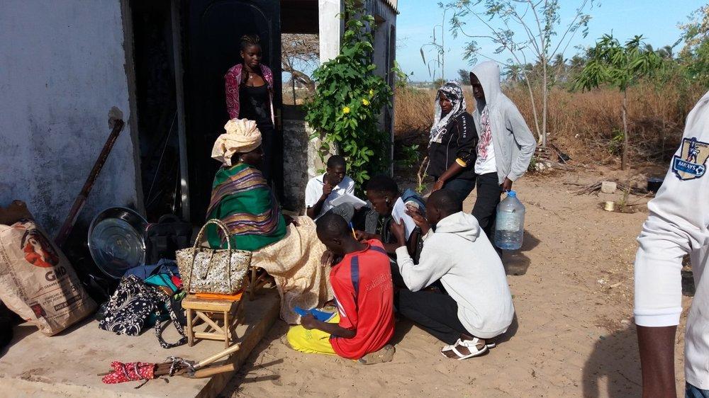 Une formatrice en micro jardinage apprenant aux membres du Club Environnement du Lycée Sergent Malamine Camara comment faire une infusion avec des feuilles de plusieurs plantes