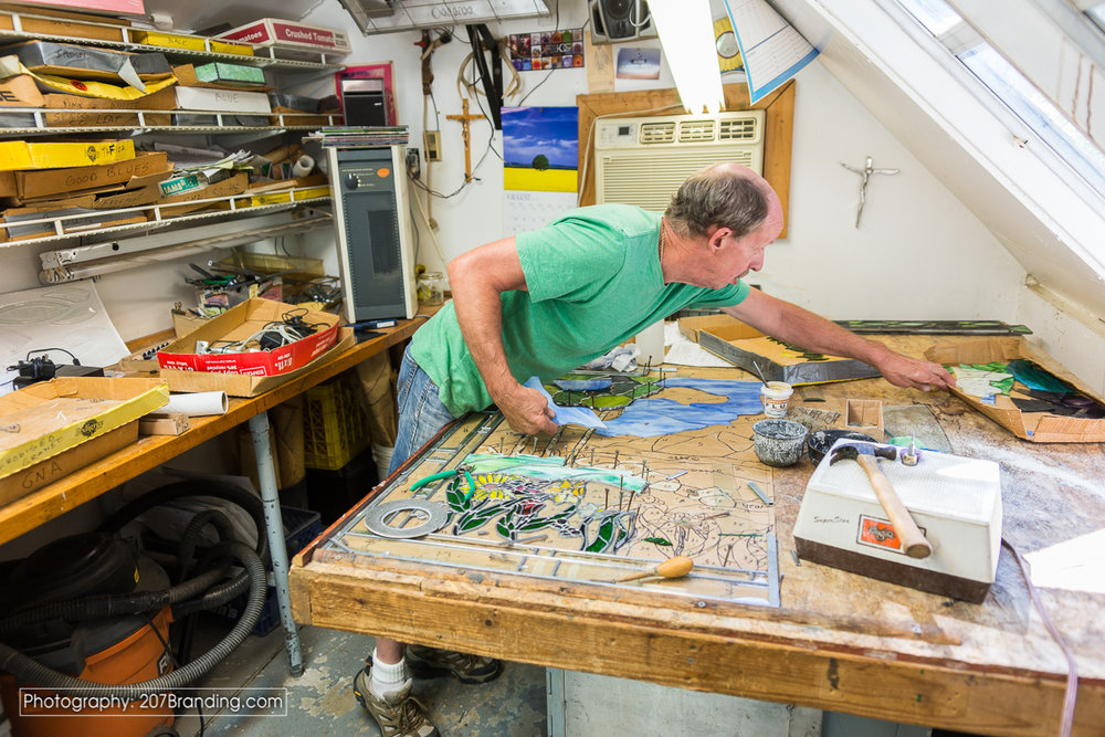 Denver Stained Glass Artist In Green Shirt Stretching Over Table