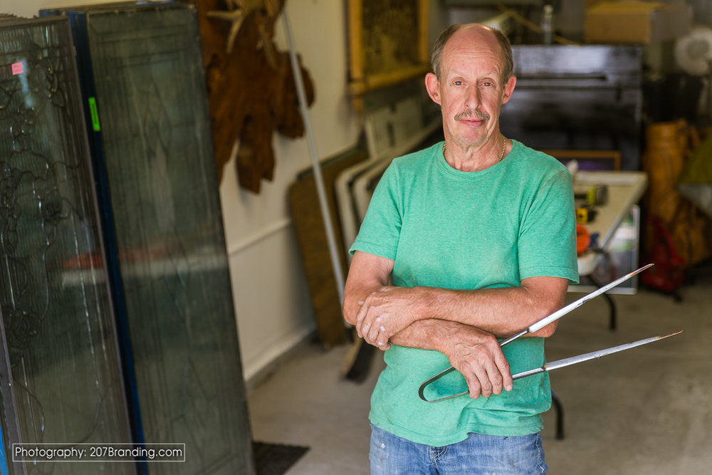 Denver Stained Glass Artist in Green short holding tools