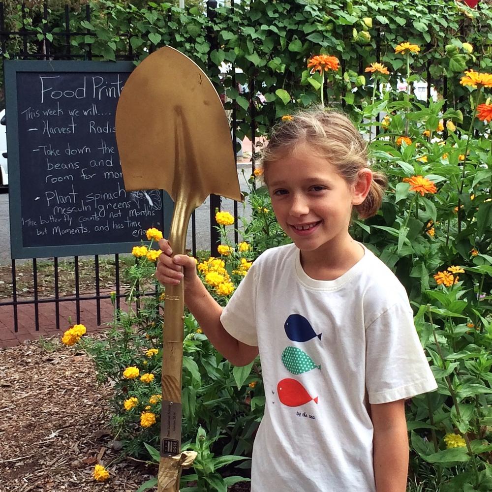 Tillie in the garden with the Golden Shovel trophy.