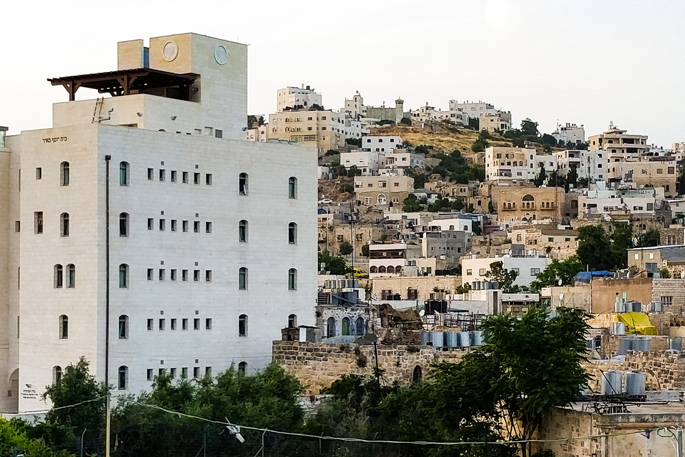 As you can see, the large building on the left with Hebrew writing has no water tanks, while all the houses to the right have silver or black tanks.