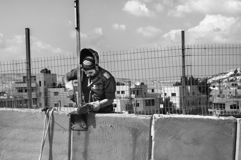 "Israeli soldier at work raising the annexation wall which serves to separate Israel from the occupied West Bank.  However, 85% of the wall veers off the green line, the geopolitical border dividing the two lands, and illegally infiltrates the occupied territory.  The wall is less about ""security"", as Israel claims, but more about creating a new border line (expanding Israeli territory), and to confine, restrict, and suffocate Palestinians from basic rights, freedoms, and joys all humans deserve--in turn pressuring residents to voluntarily relocate in order that Israel might at last become an all-Jewish State."
