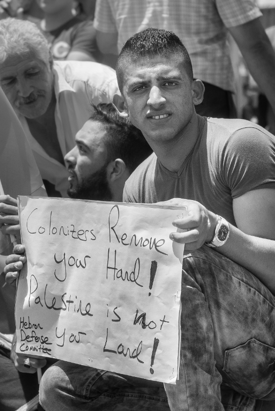 "A young man holds up a sign a few yards away from a line of armed Israeli Defense Force (IDF) soldiers at a nonviolent protest in Hebron on June 5, remembering the day of the Naksa, ""Setback"", as it is known by Palestinians and the end of the 6-Day War, as it is referred to by most Israeli Jews, which occurred in 1967 when Israel took military control over the West Bank and Gaza.  Hebron is one of the most militarized cities in the West Bank controlled an estimated 1,500 soldiers continuously on guard from street to rooftop."