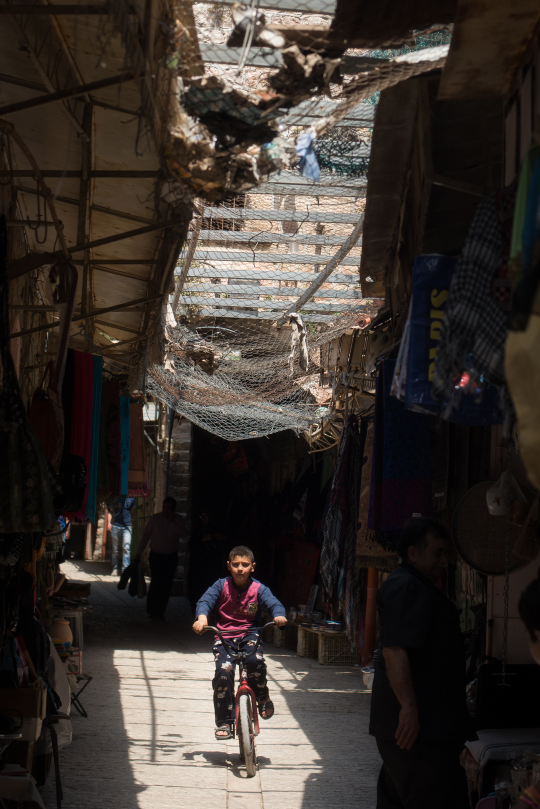 Boy rides through the souk in the Old City beneath trash-heavy wired mesh above.