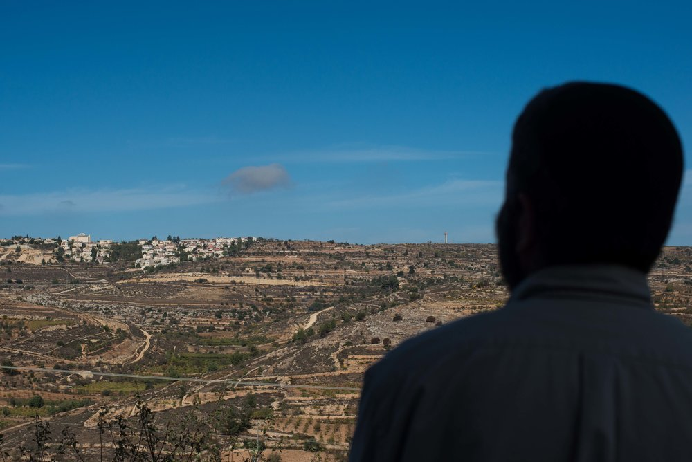 Daniel Zahavi-Asa looks off his balcony onto a neighboring illegal settlement atop a hillside across the valley known is Hebrew as Gush Etzion in the West Bank, Palestine.
