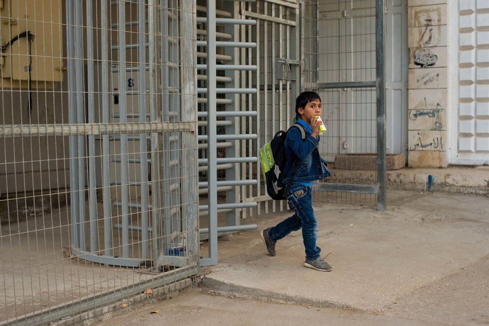 A Palestinian boy walking through a checkpoint on his way to school. Old City Hebron (H2), West Bank, Palestine.