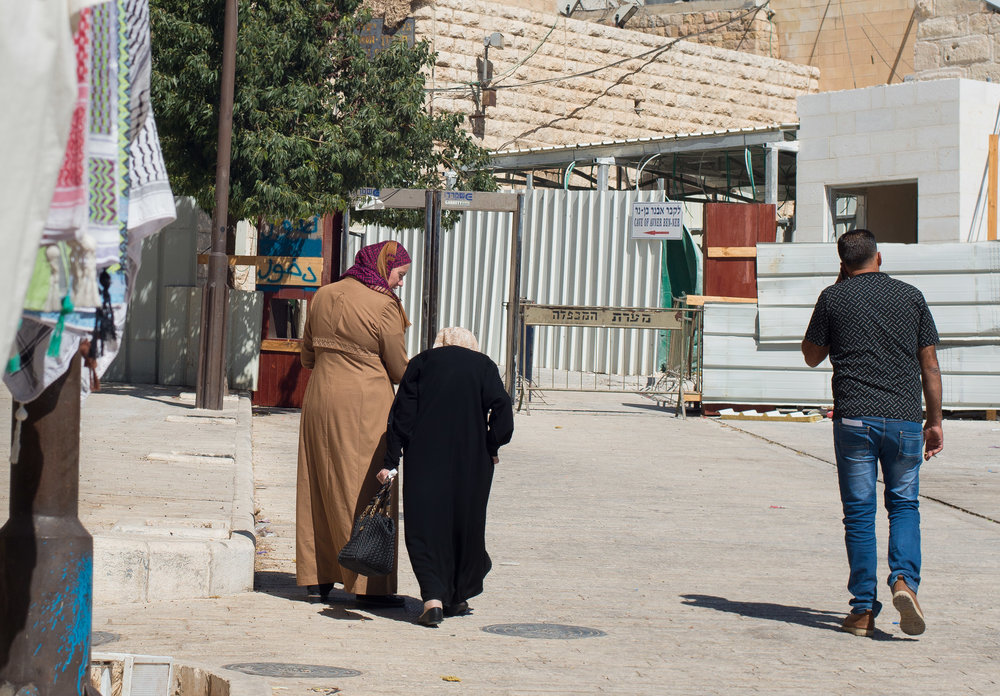 Palestinians walk toward the checkpoint directly on the other side of the Ibrahimi Mosque, just meters from another checkpoint.  Old City Hebron (H2), West Bank, Palestine.