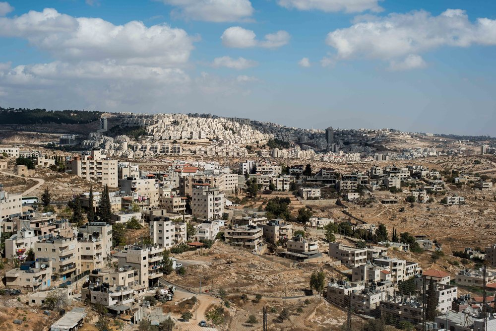 A settlement spreads across a hill above a Palestinian town in the West Bank.