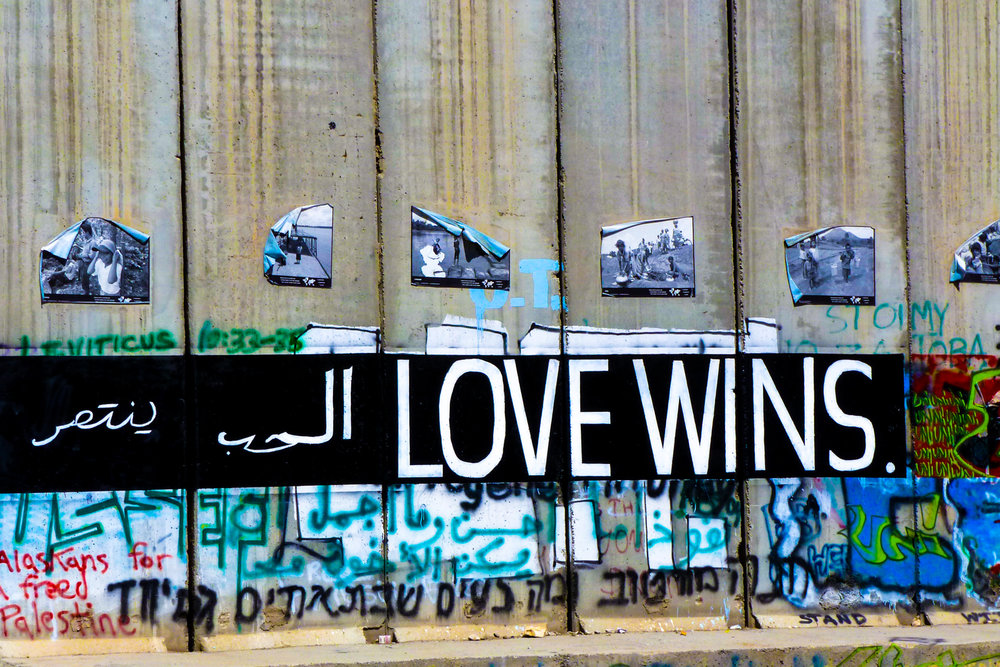 """Love Wins""- Bethlehem, Palestine, 2011    LISTEN    ""My name is Daoud and I will tell you something about what is happening here. If you want to go back to history we know that Palestine was always occupied. The Assyrians were here, the Babylonians, then the Persians, and after the Persians, the Romans, the Greek-- you know, occupation after the other. And the Ottomans were Palestine for more than 400 years. And then in 1917 Palestine was under the British Mandate. 1947 there was a plan to divide Palestine into two states. It didn't work for many reasons.  1948 Israel was established.  For the Palestinians it's called a catastrophe because this situation left more than 750,000 Palestinians without a home; and many are still living in refugee camps. Between '48 and '67, the West Bank was under Jordanian rule and the Gaza Strip was under Egyptian rule. And in the 6-Day War the Israelis occupied the West Bank, Gaza, East Jerusalem—and since then we are living under Israeli occupation.  Now the only occupation that is interested in taking land is the Israeli occu[pation].  Because they started to create facts on the ground, in terms of building settlements.  So the situation was becoming more difficult in the '70s, '80s, and then the Palestinian First Intifada started in '87.  With that situation, the Israeli authorities closed schools for Palestinians—universities…  They said, schools, places where young people come together to organize themselves politically, and we lost a generation of young people at the time who did nothing.  1991 Palestinians were not allowed to enter Israel and since then we need permission to go into Jerusalem. In the same year, 1991, the peace process started in Madrid, with the hope of peace, which was very strong. And then the peace agreements came in 1994, 1995—the Oslo Agreements—where the Israelis divided the West Bank into three zones, three areas, area A, area B, and area C. Area A are the places that are controlled by the Palestinians, and we are talking about the cities, or the center of the cities. Area B are the villages that are under civil control of the Palestinians, but military under Israeli control.  And Area C, where we are here, which is totally under Israeli control and is maybe more than 60% of the West Bank.  That means, in reality as Palestinians, until today we are not in charge of land, we are not in charge of resources, and we are not in charge of borders.  That's why it is becoming more difficult to talk about an independent Palestinians State—no land, no resources, and no borders. Now, the biggest challenge we are facing now is land confiscation, of course.  Which is going on and on since 1967. """