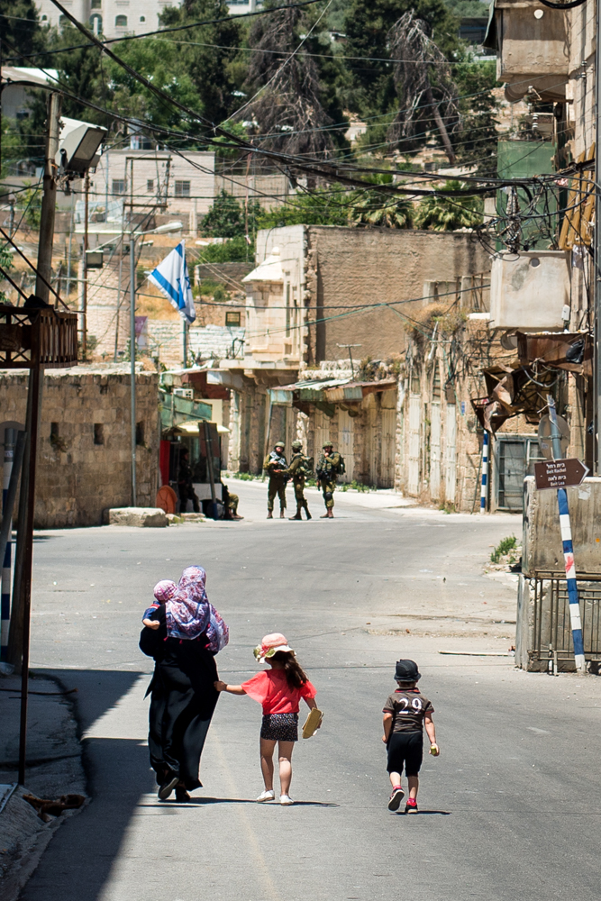 """To Exist Is To Resist""- Hebron (H2), Palestine, 2016    LISTEN    ""First let me let you know about how many checkpoints at least in Shuhada Street the place where I walk everyday to my house, from my house to other places, like to the office or to the New City. In the area located between Shuhada Street and Abrahami mosque, in general, there exist more than 38 checkpoints at the same quarter or at the same street—only a few meters away separates each others. When anyone get through electronic gates or military checkpoints you feel you have no rights. You feel like you are the one who was expected to be as a good food for a group of lions who are waiting to eat like a small sheep or a small cat because the lion has power more than the cats. You feel treated less than animal rights because if you are going to be as a dog you will be lucky to walk without the checkpoints or walk freely or to travel from place to another place. When we walk through the checkpoints and electronic gates we feel like we are losing our humanity. A million times when we get a questions from soldiers, ""where are you going to?"" or ""Take off your shoes."" ""Take off your clothes."" Or, ""Turn back."" Or, or… It's a million – a hun... more than 10s of questions. We feel we are like guilt[y] people because we are lose our simple rights of life like right of living and right of movement."""