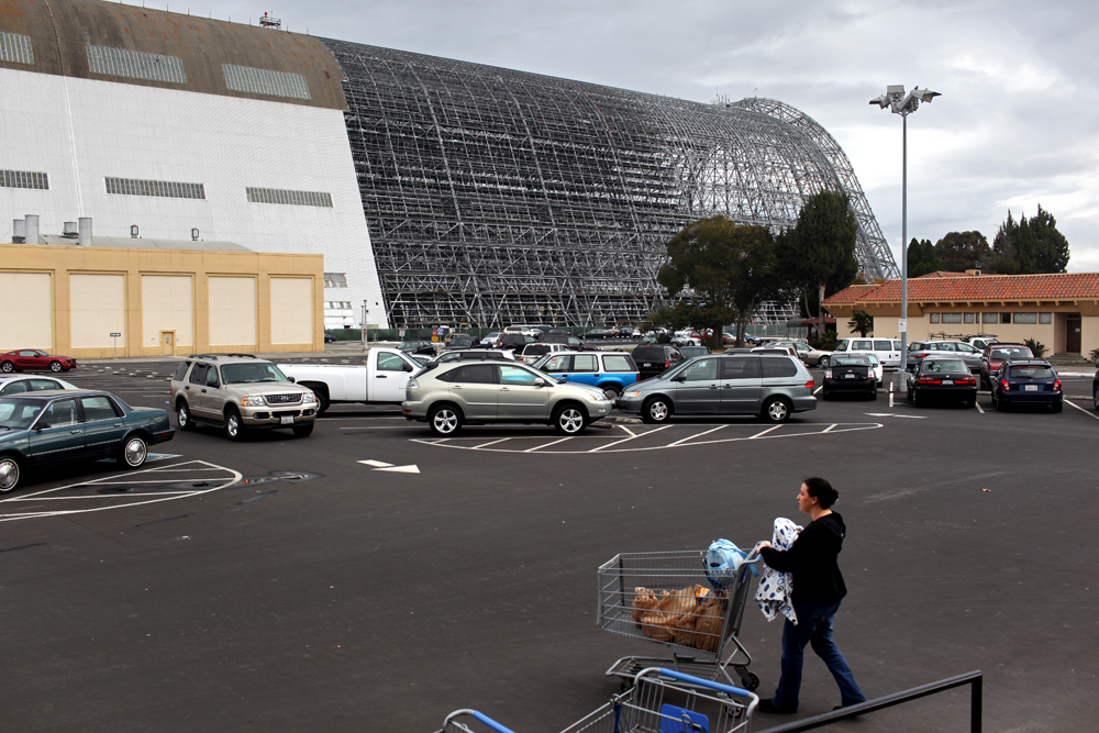 Carrying Jasper in front of her, Shelby pushes her grocery cart across the commissary parking lot. Hangar One is being stripped and cleaned of abestos in the background.