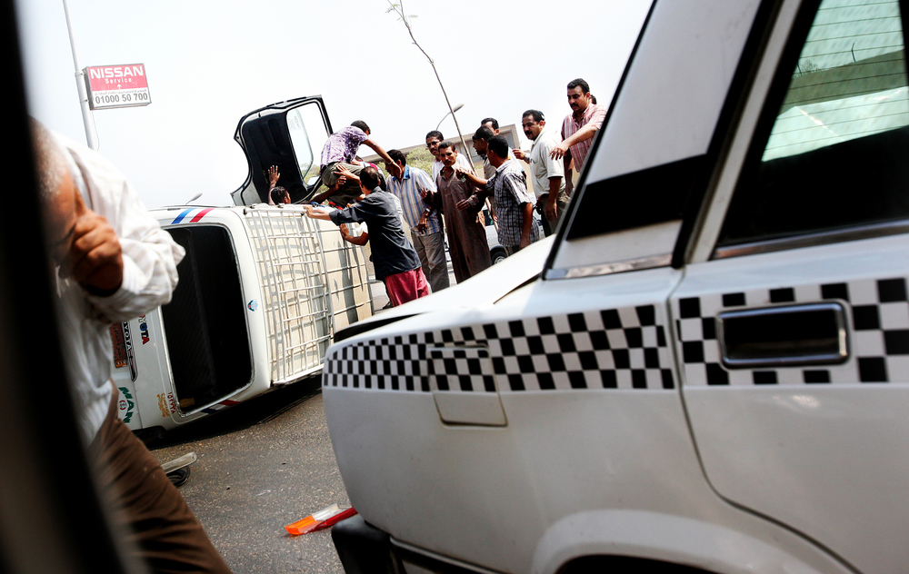 After a collision, men are pulled out of a commuter van on a highway in Cairo, Egypt.