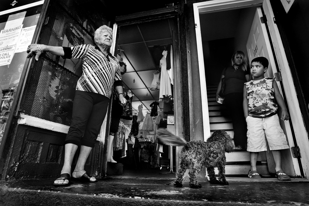 A shop owner sharing a building with apartment dwellers, yells across the street in the Latino neighborhood in Chicago.